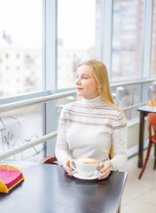beautiful girl is drinking coffee and looking thoughtfully into window. pretty blonde sat down at a table in a cafe with a cup of coffee