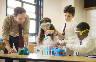 Male teacher helping students (8-9, 10-11) with science experiment