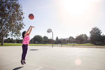 Girl (6-7) playing basketball