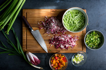 Assorted vegetables chopped on wooden cutting board