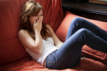 Young woman laughing on couch