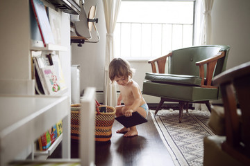 Shirtless girl (2-3) crouching and holding digital tablet