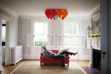 Young man lying on sofa and looking at colorful balloons
