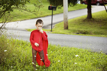 Boy wearing superhero outfit smelling flowers