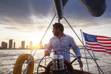 Man standing in sailboat and looking at skyline in sunset