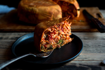 Slice of homemade timpano on plate