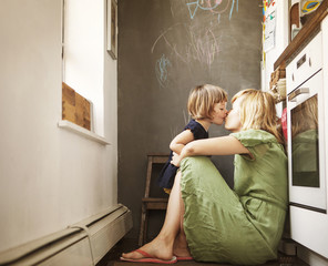 Mother kissing daughter (2-3) in kitchen