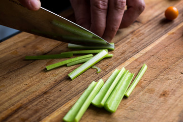 Person chopping celery on wooden chopping board