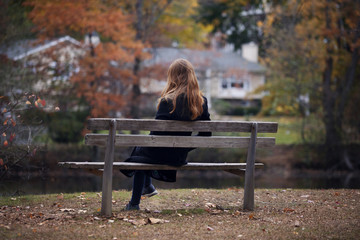 Young woman sitting on bench in autumn