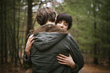 Young couple embracing in woods