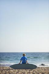 Boy (8-9) sitting on surfboard on beach
