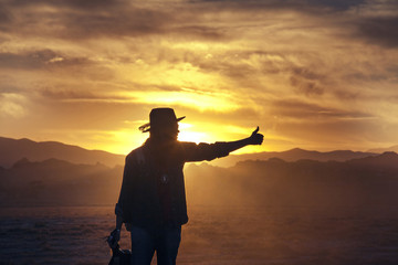 Man hitchhiking on road by desert at sunset
