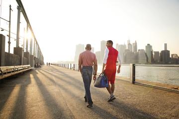 Rear view of two men walking along East river in Brooklyn