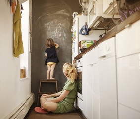 Daughter drawing on board while mother looking at her in kitchen