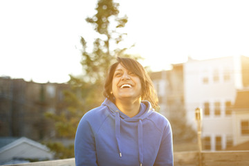 Young woman in blue sweatshirt laughing