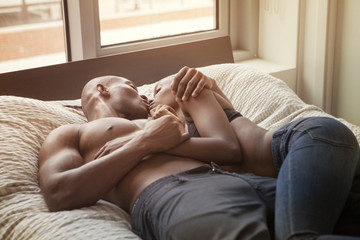 Couple kissing each other while lying on bed