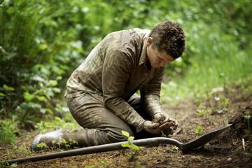 Man inspecting dirt on rainforest floor