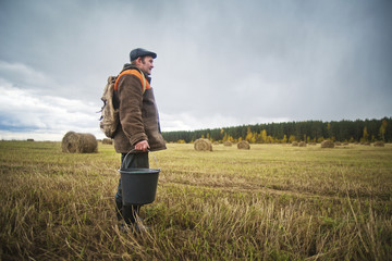 Farmer standing in field and holding bucket