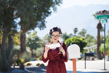 Young woman in bathrobe and curlers taking letter from mailbox