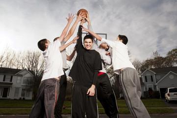 Portrait of tall friend (14-15 ) keeping basketball away from friends (12-13, 14-15 )