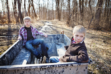 Two young boys (8-9, 14-15) riding in back of tractor cart