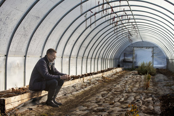 Mature man sitting in green house