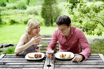 Smiling couple having drink while sitting in backyard