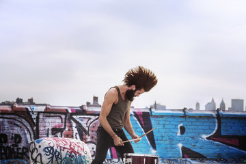 Young man playing drum while standing outdoors