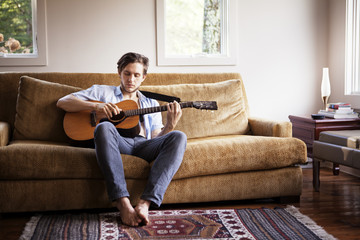 Young man playing acoustic guitar on couch