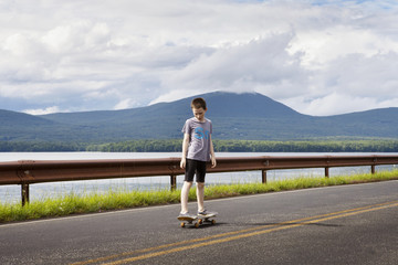 Boy (10-11) skateboarding on empty road