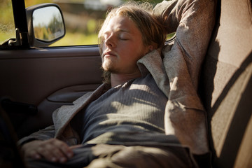 Young man sleeping in pick-up truck