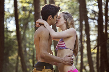Young man kissing his girlfriend (16-17) in forest