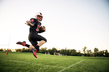 American football player jumping in field