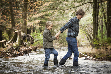 Side view of father with son (8-9) walking through stream