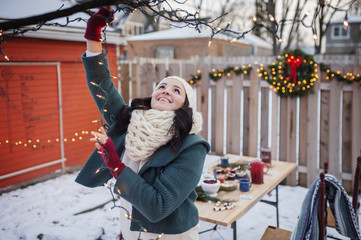 Smiling young woman decorating backyard during Christmas