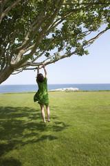 Woman swinging on tree near ocean