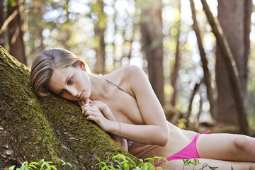 Teenage girl (16-17) lying in forest
