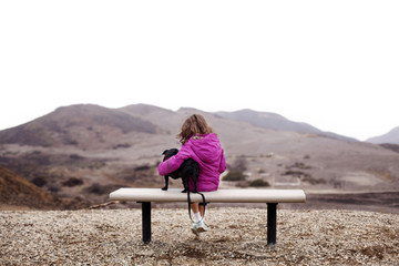 Girl (6-7) sitting on bench with dog