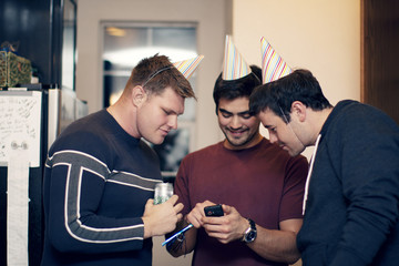 Friends at party looking at cell phone