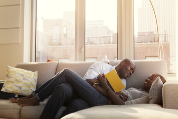 Smiling couple romancing on sofa at home