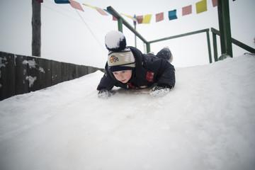 Boy (2-3) sledding down slope
