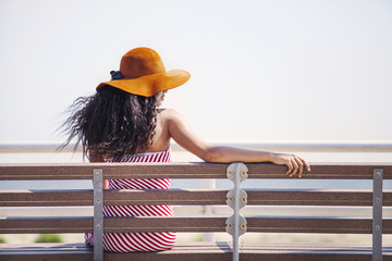 Girl (12-13) wearing sun hat sitting on bench