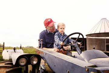 Grandfather with young grandson (10-11) on tractor