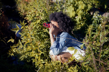 Girl (8-9) looking through binoculars