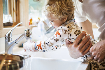Father holding son washing hands in kitchen sink