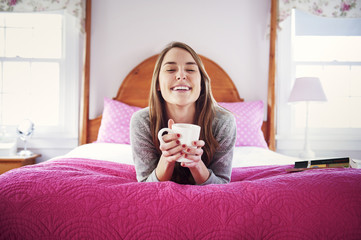 Woman on bed with coffee and book
