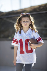 Portrait of girl (8-9) wearing football uniform and holding football