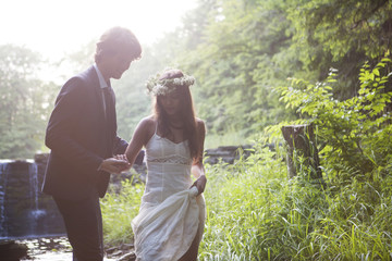Newly weds holding hands in forest