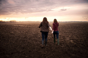 Two Girlfriends walking through field at sunrise