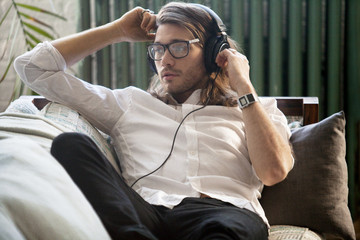 Young man sitting on sofa and listening music